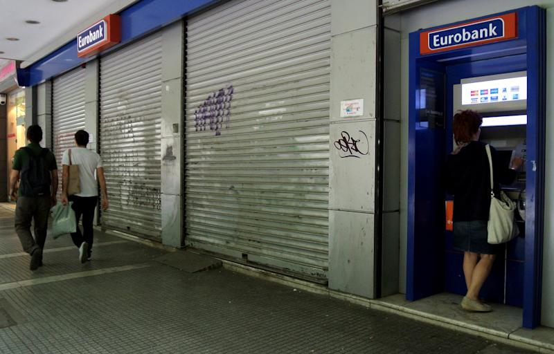 A woman uses an ATM machine outside Greece's Eurobank at the northern port city of Thessaloniki, Greece, on Wednesday, May 23, 2012. Greece's four biggest commercial banks will receive an euro 18 billion ( $23 billion) cash infusion from the European bailout fund. (AP Photo/Nikolas Giakoumidis)