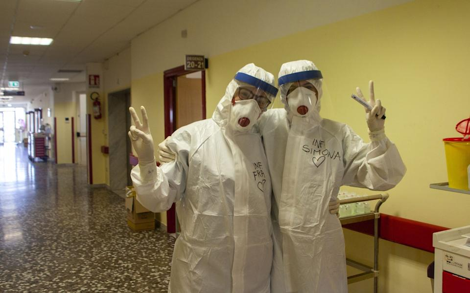 Two nurses pose for the camera wearing personal protective equipment whilst on shift. New infections from Covid in the region rapidly increased in the last 24 hours, with 485 positive results - Donato Fasano/Getty Images