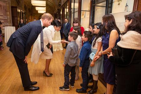 Britain's Prince Harry, Duke of Sussex and Meghan, Duchess of Sussex talk with children as they visit the Natural History Museum in London, Britain, February 12, 2019. Heathcliff O'Malley/Pool via REUTERS