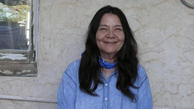 Leslie Marmon Silko stands against a wall and smiles.