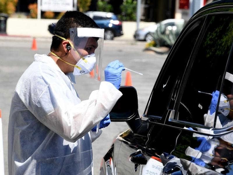 A worker wearing personal protective equipment gathers coronavirus tests administered from a drive-thru testing site.