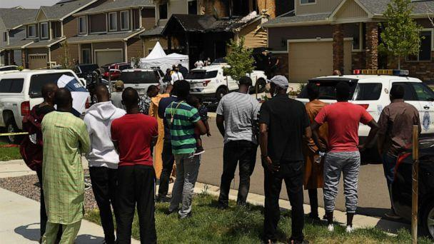 PHOTO: Members of the Senegalese community watch as bodies are removed from a burnt home after five people were killed inside on Aug. 5, 2020, in Denver. (Denver Post via Getty Images, FILE)