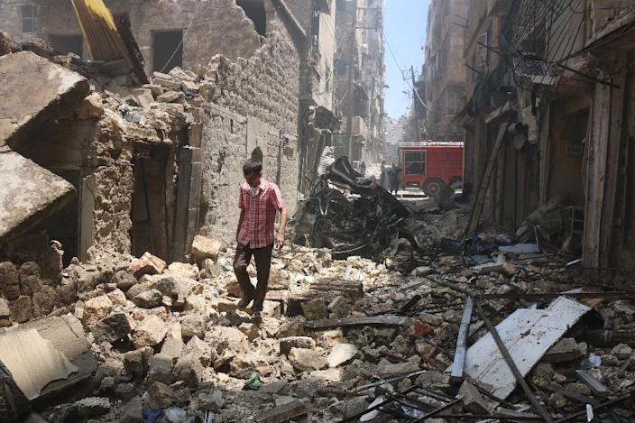 A man walks on the rubble of a destroyed building following reported air strikes by Syrian forces in the rebel-held Al-Shaar neighbourhood of Aleppo, on June 8, 2016 (AFP Photo/Thaer Mohammed)