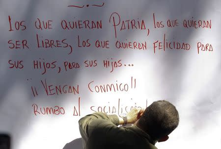 File photo of late Venezuelan President Chavez writing a message after signing to support his proposal of constitutional change in Caracas