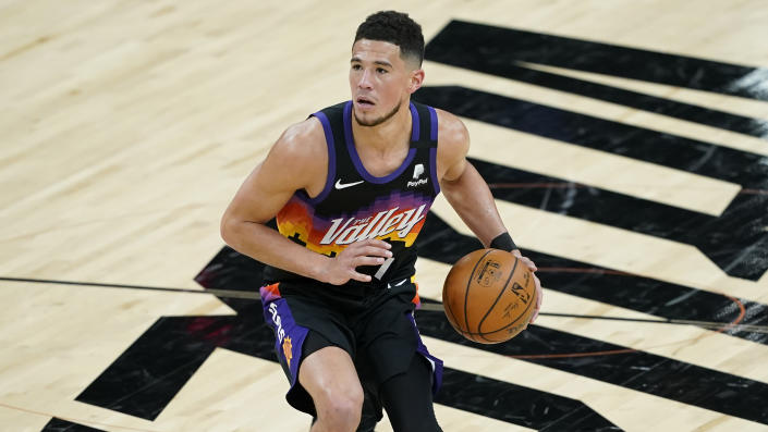 Phoenix Suns guard Devin Booker (1) against the Philadelphia 76ers during the second half of an NBA basketball game, Saturday, Feb. 13, 2021, in Phoenix.(AP Photo/Matt York)