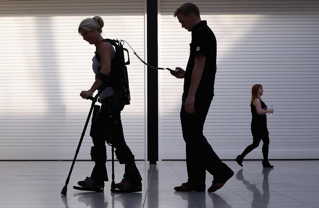 LONDON, ENGLAND - OCTOBER 21:  Amanda Boxtel (L), who is paralysed, is helped to walk with the aid of the new 'Bionic Exoskeleton' during its launch at the Excel centre on October 21, 2011 in London, England. The device developed by Ekso Bionics is a wearable, battery-powered, robotic exoskeleton, designed to aid wheelchair users and those who have suffered from spinal chord injuries to stand and walk.  (Photo by Dan Kitwood/Getty Images)