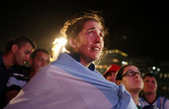 An Argentine fan cries as she watches Argentina's defeat to Germany in their 2014 World Cup final match, on Copacabana beach in Rio de Janeiro July 13, 2014. REUTERS/Pilar Olivares (BRAZIL - Tags: SOCCER SPORT WORLD CUP TPX IMAGES OF THE DAY)
