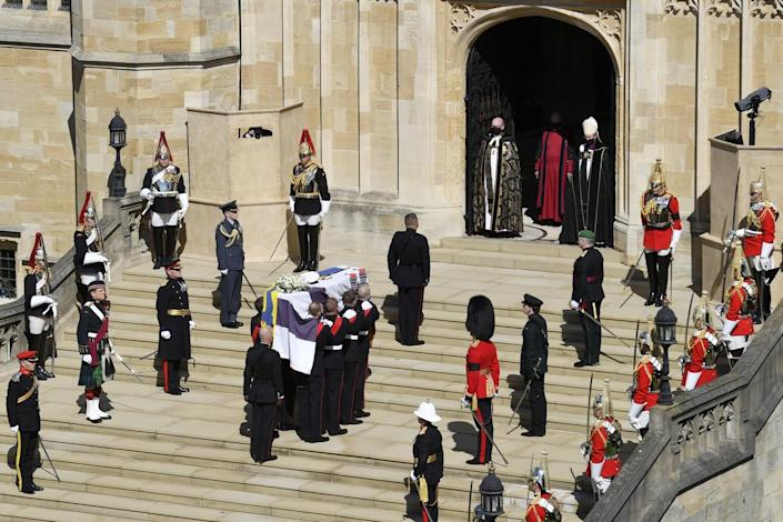 The coffin is carried up the steps at St. George's Chapel by pallbearers as other military members stand nearby.