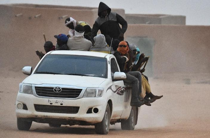 A pick-up truck carrying migrants rides through Agadez on June 1, 2015 en route to Libya (AFP Photo/Issouf Sanogo)