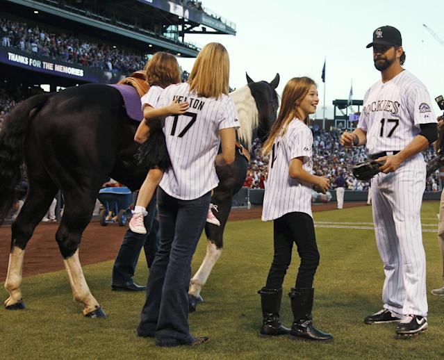 After being given a gelding paint horse named Tobiano as a retirement present, Colorado Rockies first baseman Todd Helton, right, joins his daughter Tierney Faith, second from right, and his wife Christy and daughter Gentry Grace in looking over the horse before the Rockies played the Boston Red Sox in a baseball game in Denver on Wednesday, Sept. 25, 2013. Helton, who will retire at season's end, was playing in his final home game for the Rockies. (AP Photo/David Zalubowski)