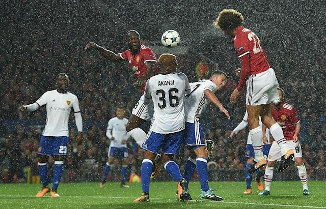 Manchester United's midfielder Marouane Fellaini (R) heads the opening goal during their UEFA Champions League Group A football match against Basel at Old Trafford on September 12, 2017 (AFP Photo/Oli SCARFF )