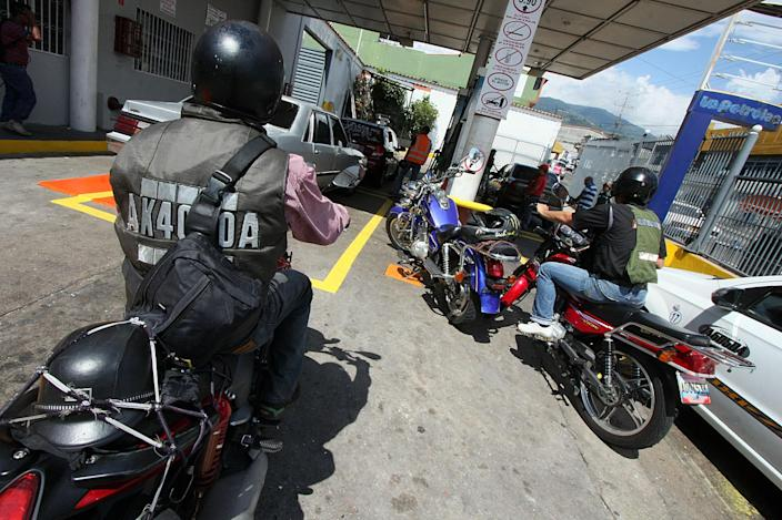 Motorcyclists line up to buy fuel at a petrol station in the state of Tachira, Venezuela on May 26, 2014 (AFP Photo/George Castellano)