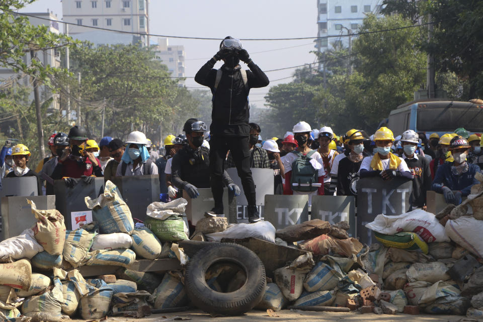 Protesters take positions behind a barricades as police gather in Yangon, Myanmar, Sunday, March 7, 2021. The escalation of violence in Myanmar as authorities crack down on protests against the Feb. 1 coup is raising pressure for more sanctions against the junta, even as countries struggle over how to best sway military leaders inured to global condemnation. (AP Photo)