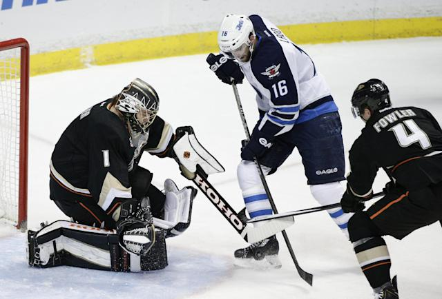 Winnipeg Jets' Andrew Ladd (16) tries to score against Anaheim Ducks goalie Jonas Hiller, left, of Switzerland, as he is defended by Ducks' Cam Fowler during the first period of an NHL hockey game, Tuesday, Jan. 21, 2014, in Anaheim, Calif. (AP Photo/Jae C. Hong)