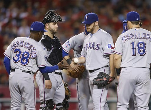 Texas Rangers manager Ron Washington, left, removes starting pitcher Ryan Dempster, center right, during the fourth inning of a baseball game against the Los Angeles Angels in Anaheim, Calif., Tuesday, Sept. 18, 2012. (AP Photo/Jae C. Hong)