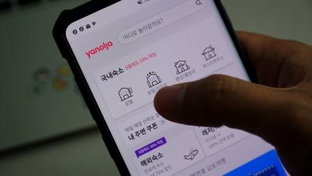 A couple looks at South Korea's accommodation-booking app on a mobile phone, in Seoul