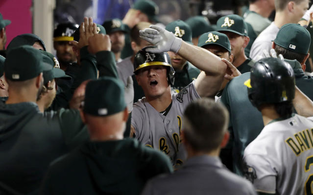 Oakland Athletics' Matt Chapman, center, celebrates his two-run home run with teammates in the dugout during the ninth inning of a baseball game against the Los Angeles Angels on Wednesday, Sept. 25, 2019, in Anaheim, Calif. (AP Photo/Marcio Jose Sanchez)