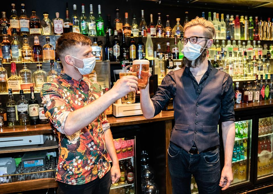 Bar staff celebrate in the Showtime Bar at 00:00 in Huddersfield, West Yorkshire, as indoor hospitality and entertainment venues reopen to the public