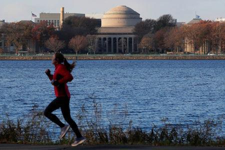 A jogger passes by the Massachusetts Institute of Technology (MIT) along the Charles River in Cambridge, Massachusetts, U.S., November 21, 2018. REUTERS/Brian Snyder