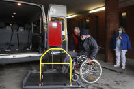 An ambulance operator helps a a patient at the hospital for the homeless in Budapest, Hungary, Wednesday, April 14, 2021. A bitter conflict has emerged between Hungary's right-wing government and the liberal leadership of the country's capital city over a hospital for the homeless that may soon have to close. The Budapest hospital provides medical and social services and shelter to more than 1,000 people annually. But the Hungarian government has ordered it to vacate the state-owned building it occupies. Budapest's mayor says the eviction will risk the lives of the hospital's homeless patients as Hungary struggles with a deadly COVID-19 surge.. (AP Photo/Laszlo Balogh)