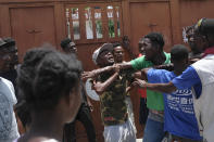 People fight outside a Red Cross center after a group entered and ran off with mattresses in Les Cayes, Haiti, Friday, Aug. 20, 2021, six days after a 7.2 magnitude earthquake hit the area. (AP Photo/Matias Delacroix)
