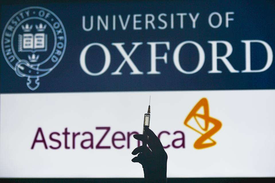 An illustrative image of a hand holding a medical syringe in front of the University of Oxford AstraZeneca logos displayed on a screen. On Monday, February 1, 2021, in Dublin, Ireland. (Photo by Artur Widak/NurPhoto via Getty Images)