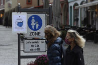 People pass a sign reading 'Face masks mandatory from here' in the deserted city of Berchtesgaden, Germany, Monday, Oct. 26, 2020. Authorities have posed the Berchtesgaden region under a lockdown since Oct. 20, 2020 due to a rising number of cases of the pandemic COVID-19 disease caused by the SARS-CoV-2 coronavirus in the district of Berchtesgadener Land. Local authorities in Bavaria's Rottal-Inn county, on the border with Austria, said Monday that the restrictions will begin at midnight. (AP Photo/Matthias Schrader)