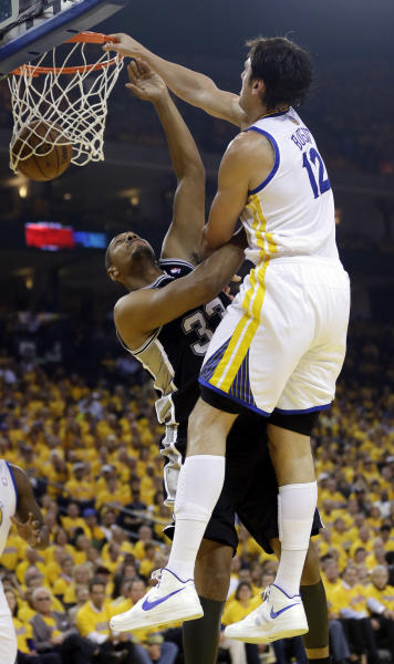 Golden State Warriors' Andrew Bogut, right, dunks over San Antonio Spurs' Boris Diaw during the first half of Game 3 of a Western Conference semifinal NBA basketball playoff series in Oakland, Calif., Friday, May 10, 2013. (AP Photo/Marcio Jose Sanchez)