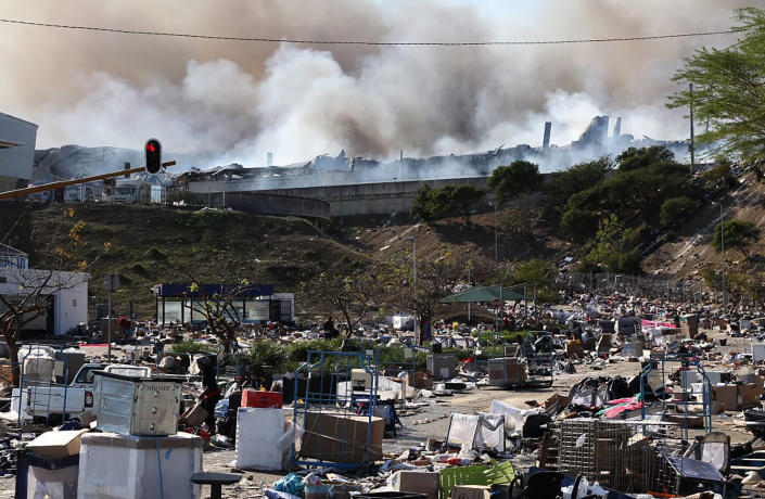 A factory burns in the background while empty boxes litter the foreground from looted goods being removed, on the outskirts of Durban, South Africa, Wednesday, July 14, 2021 in ongoing unrest. Rioting has continued which was sparked by the imprisonment last week of ex-President Jacob Zuma resulting in days of looting in two of the country's nine provinces. (AP Photo)
