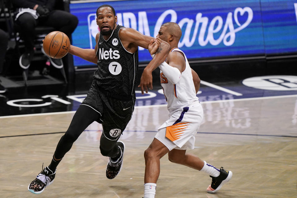 Brooklyn Nets forward Kevin Durant (7) becomes entangled with Phoenix Suns guard Chris Paul during the third quarter of an NBA basketball game, Sunday, April 25, 2021, in New York. (AP Photo/Kathy Willens)