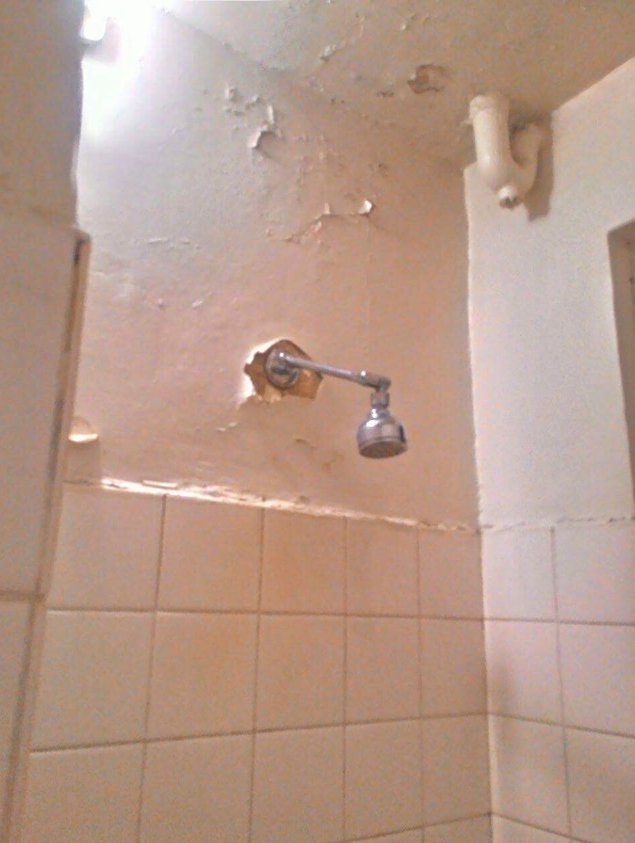 The hotel's show with an exposed shower head and peeling paint taken by an angry customer