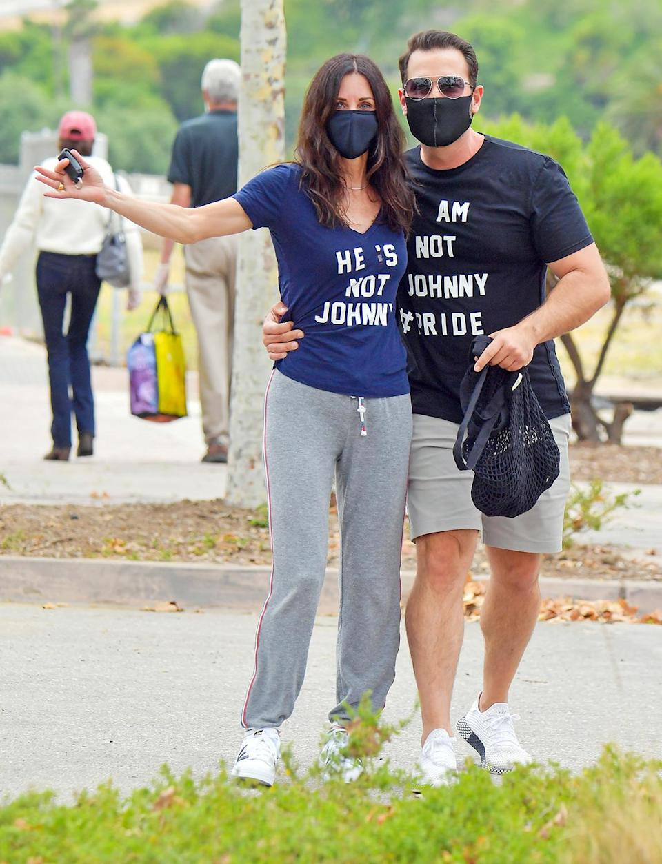 <p>Courteney Cox and her friend wear cheeky shirts in L.A. on Sunday to let everyone know that the <i>Friends</i> star is not hanging out with boyfriend Johnny McDaid, who is currently quarantining in Europe and has been since the start of the pandemic. </p>