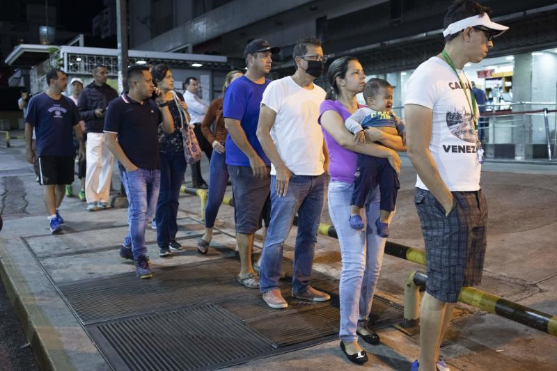 People line up outside a supermarket after President Nicolás Maduro ordered residents in the capital of Caracas and six states to stay home under a quarantine in a bid to control the spread of the coronavirus in Caracas, Venezuela, Sunday, March 15, 2020. (AP Photo/Ariana Cubillos)