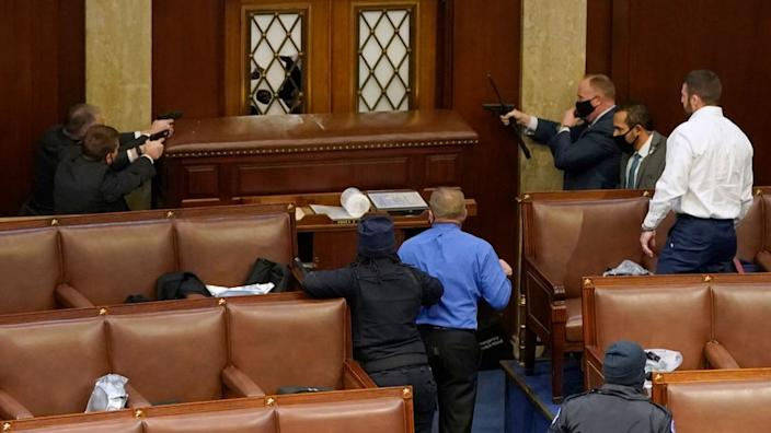 Capitol police point guns at a protester from inside the House chamber