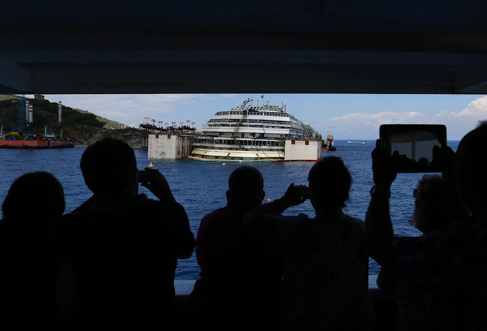 Tourists take a pictures from a ferry boat of the capsized cruise liner Costa Concordia as they arrive outside Giglio harbour July 13, 2014. The refloat operation for Costa Concordia is expected to begin on July 14 and be completed on July 21. REUTERS/Alessandro Bianchi (ITALY - Tags: DISASTER TRAVEL TRANSPORT)