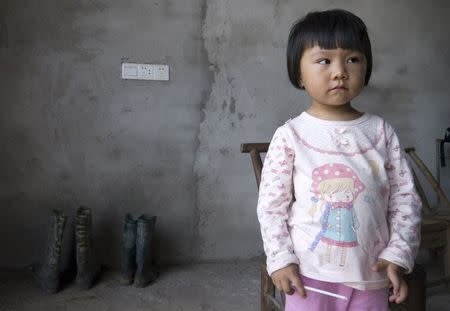 Two-year-old Xu Yilin, whose blood, according to her family, has been shown to have almost three times the national limit for lead exposure in children, stands in a neighbor's house in Dapu town, Hunan province, June 25, 2014. REUTERS/Alexandra Harney