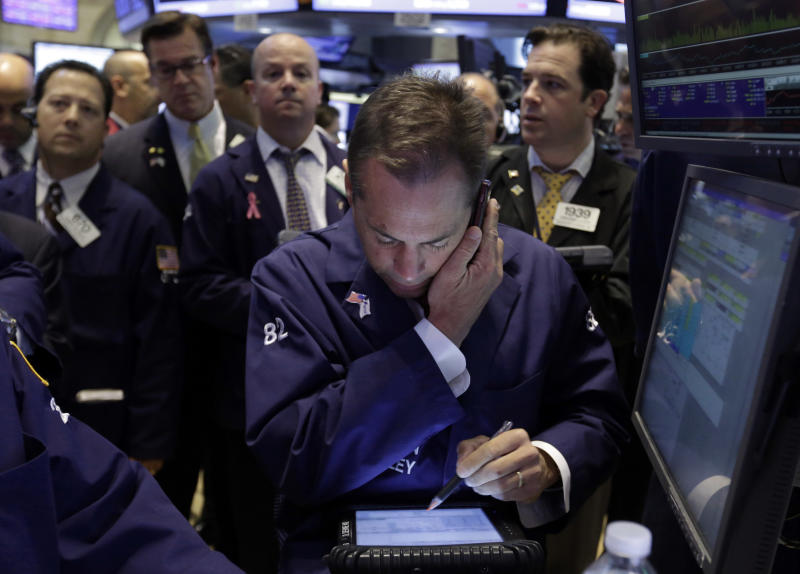 Trader Dudley Devine, foreground, uses his mobile phone and handheld device, as he works on the floor of the New York Stock Exchange Wednesday, June 19, 2013. Stocks edged lower in early trading on Wall Street Wednesday as investors waited for word from the Federal Reserve. (AP Photo/Richard Drew)