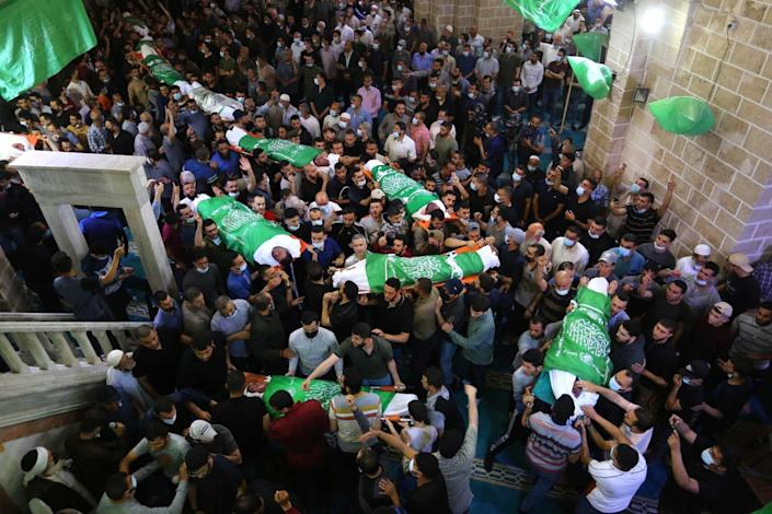 Bodies wrapped in Palestinian flags are carried by crowds