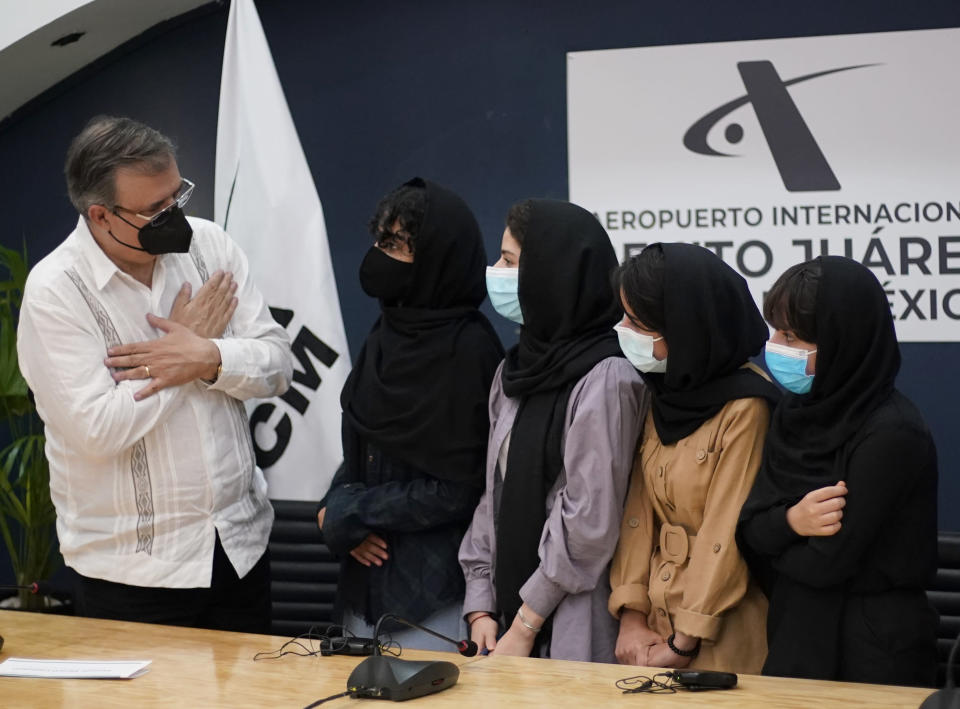 Mexico´s Foreign Minister Marcelo Ebrard, left, welcomes members of the original Afghan all-girls robotics team, who have received threats from the Taliban, after arriving at the Benito Juarez International Airport in Mexico City, Tuesday, Aug. 24, 2021. After extensive international efforts and coordination from a diverse group of volunteers to evacuate the team, the girls are now begging the international community to help get their family to safety with them. (AP Photo/Eduardo Verdugo)