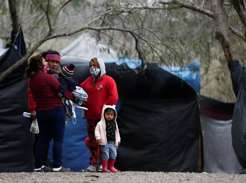 Asylum seekers stand inside a migrant encampment in Matamoros