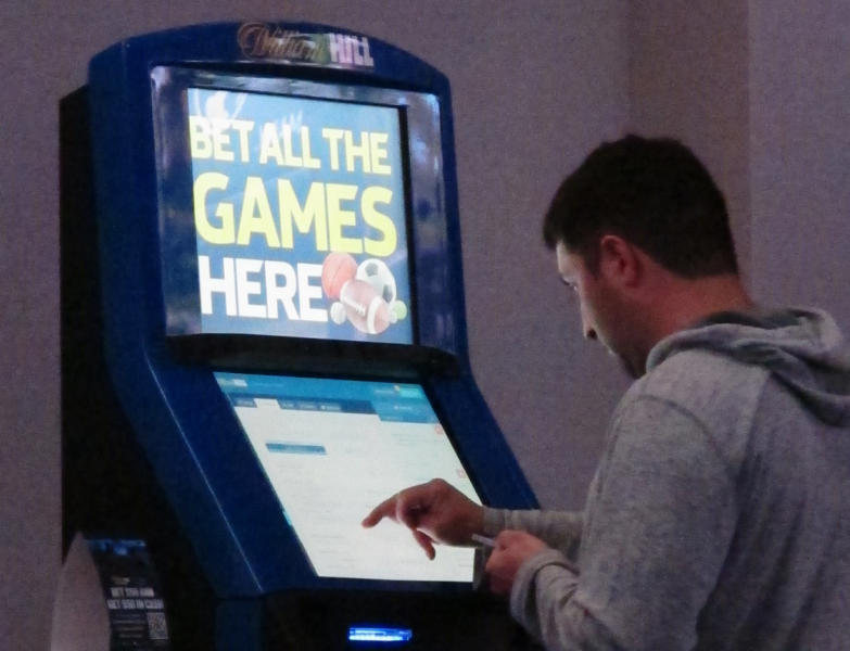 This June 21, 2019 photo shows a gambler making bets at a William Hill kiosk inside the Ocean Casino Resort in Atlantic City, N.J. On Monday, June 24, William Hill announced it is donating $50,000 it received from a lawsuit accusing rival FanDuel of copying its betting guide to a New Jersey college to fund creative writing classes. (AP Photo/Wayne Parry)