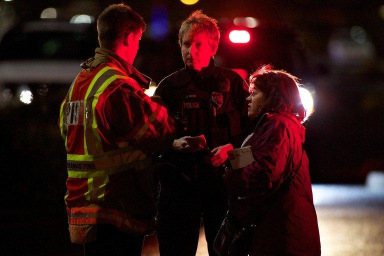 A police officer and firefighter speak to a woman outside the Clackamas Town Center during a shooting on December 11, 2012 in Clackamas, Oregon. At least two people were killed when a masked gunman opened fire at the mall, sparking panic before apparently turning the gun on himself, police said