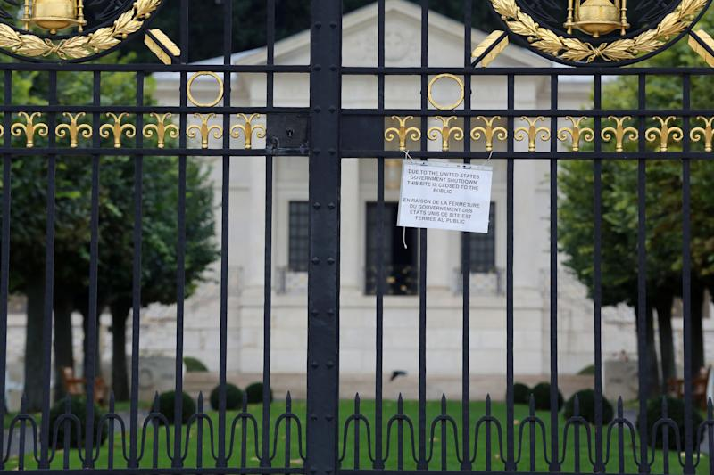 A notice advising visitors in English and French that the American Cemetery is closed due to the partial shutdown of the U.S. federal government hangs from the gates of the cemetery in Suresnes, west of Paris, Tuesday Oct. 1, 2013. The U.S. plunged into a partial government shutdown for the first time in nearly two decades because of a budget impasse in Congress, closing public sites in the U.S. and abroad. (AP Photo/Remy de la Mauviniere)
