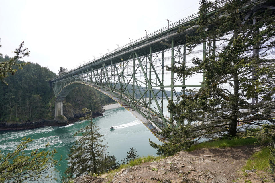 The Deception Pass Bridge, nearly 1,000-feet long and about 180-feet above the waters below, is covered in scaffolding as work to replace corroded steel and paint the structure continues Thursday, April 29, 2021, in Deception Pass, Wash. Raising state taxes to improve roads and bridges is one of the few things many Republican and Democratic lawmakers have agreed on in recent years. Those efforts have slowed to a crawl this year, even as lawmakers acknowledge a widening gap between needed work and the money to pay for it. (AP Photo/Elaine Thompson)