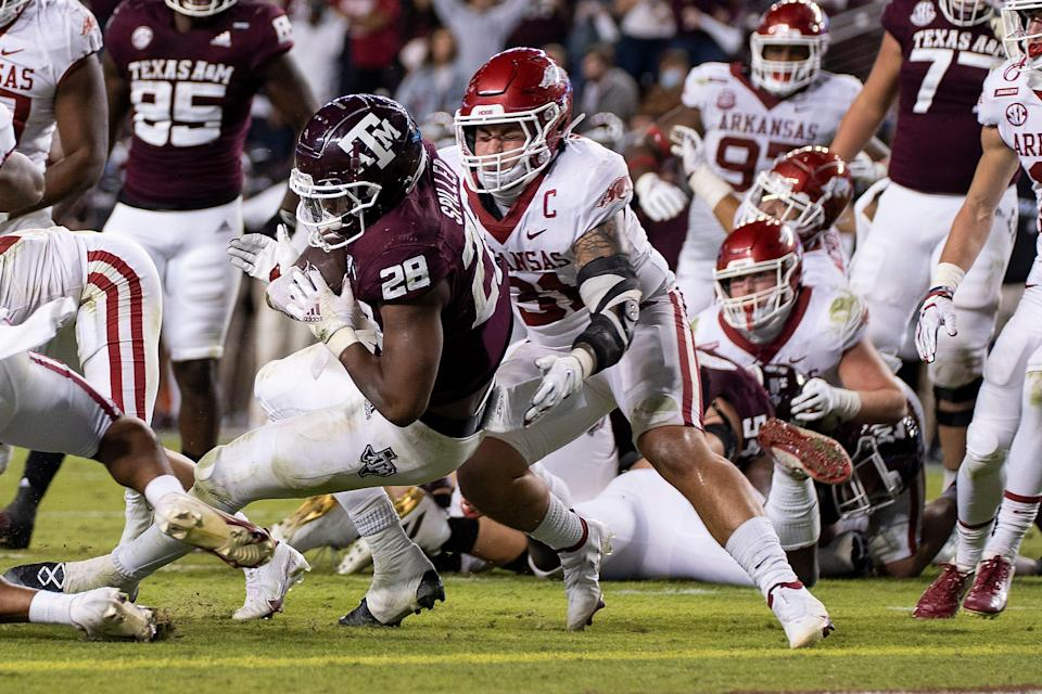 Texas A&M running back Isaiah Spiller (28) rushes for a touchdown as Arkansas linebacker Grant Morgan (31) tries to make a tackle during their game in 2020 in College Station, Texas.