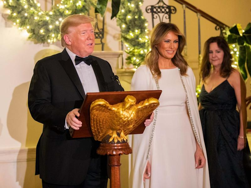 President Donald Trump, flanked by first lady Melania Trump, speaks in the Grand Foyer of the White House during the Congressional Ball on 12 December 2019: Manuel Balce Ceneta/AP