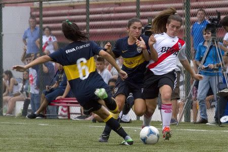 Players from Boca Juniors (L) and River Plate women's soccer clubs battle for the ball in a league match in Buenos Aires December 8, 2013. REUTERS/Carolina Camps