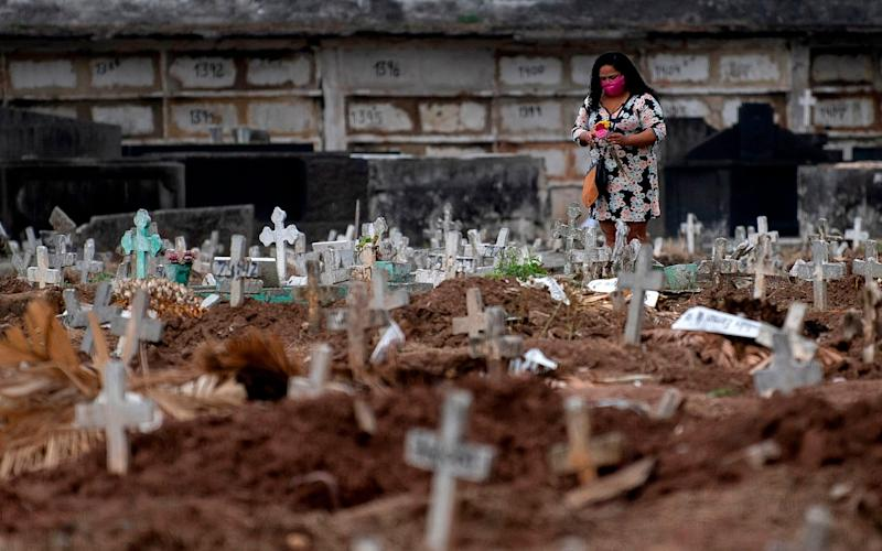 A woman visits a relative's grave at a cemetery in Rio de Janeiro, Brazil - MAURO PIMENTEL/AFP