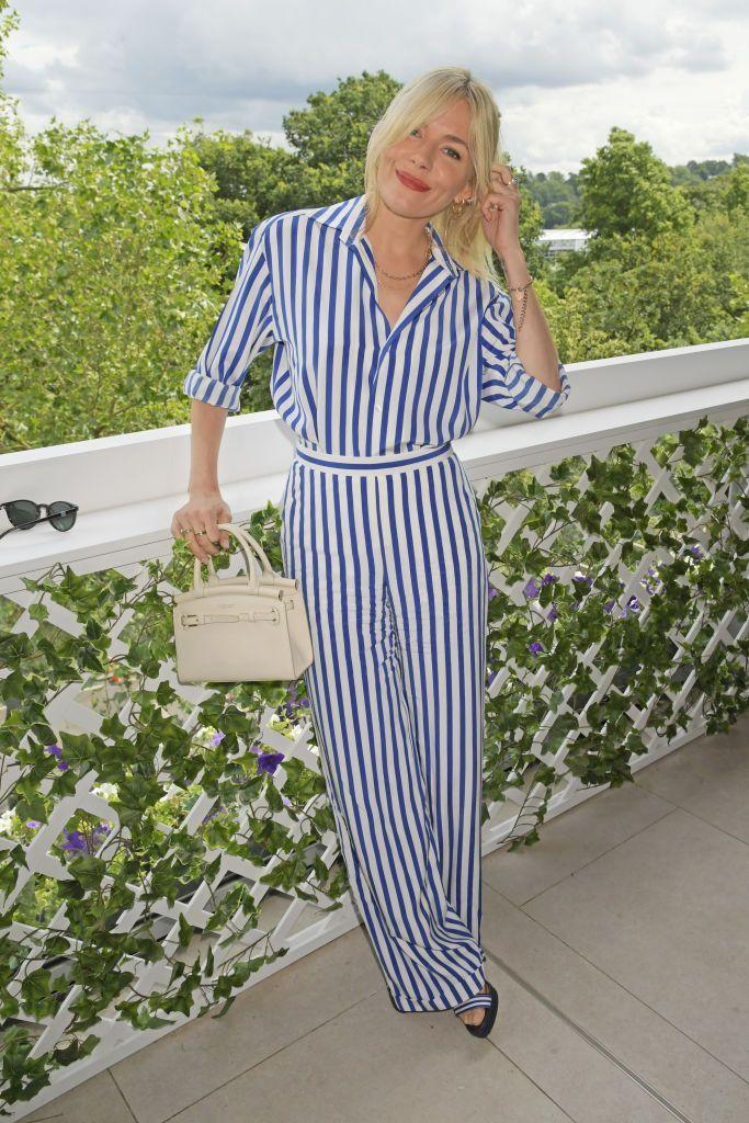<p>Miller took a leaf out of the Duchess of Sussex's book in a striped Ralph Lauren shirt.</p>