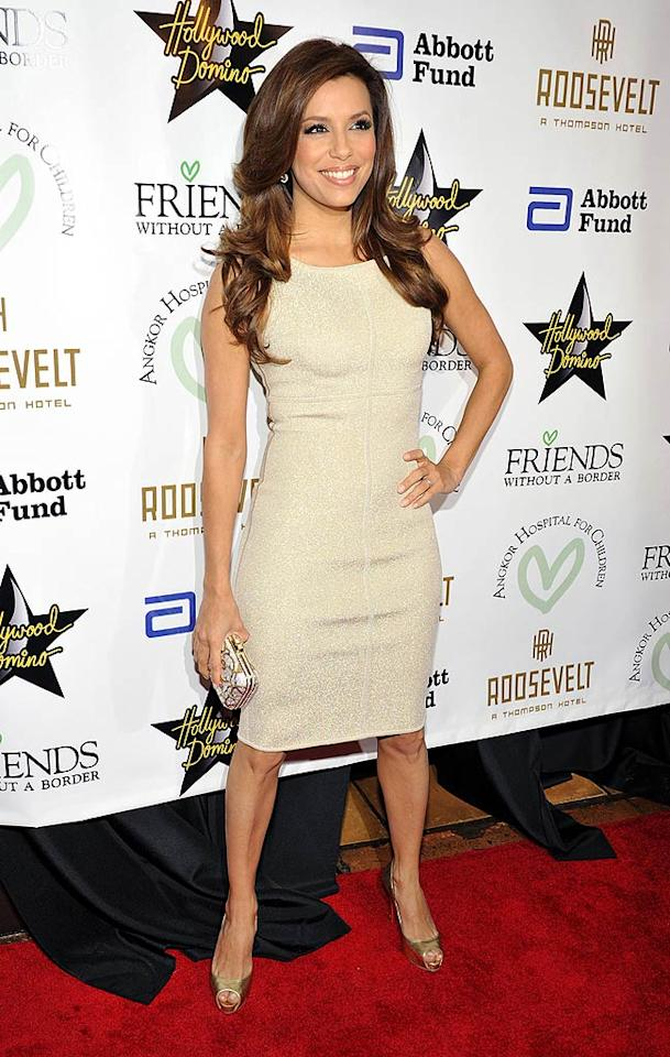 "Eva Longoria Parker goes for gold, donning a figure-hugging frock and sparkly accessories. She and other celebs walked the red carpet at the glitzy Roosevelt Hotel for the Friends Without A Border gala. Toby Canham/<a href=""http://www.gettyimages.com/"" target=""new"">GettyImages.com</a> - December 10, 2009"